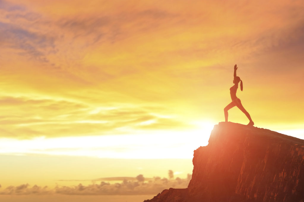 Young woman silhouette practicing yoga on top of mountain with sunshine at sunset